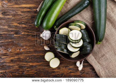 zucchini sliced and whole zucchini lying on the board lies next to the garlic napkin of burlap
