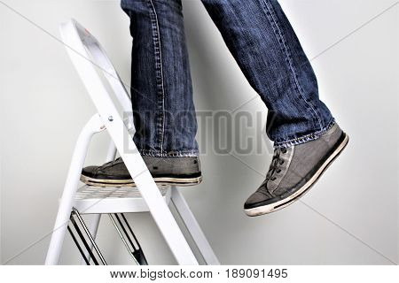 Anonymous man reaching on top of ladder climbing, indoors studio people shot.