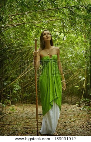 Pacific Islander woman walking in bamboo forest