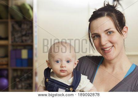Caucasian mother holding baby in yoga studio