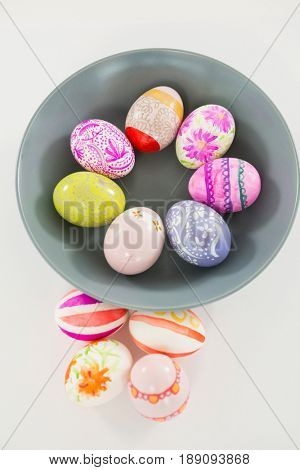 Close-up of bowl with painted Easter eggs on white backgroundwhite background, easter, easter egg, egg, dyed, painted, design, pattern, shape, bowl, multicolored, colorful, decoration, organic,