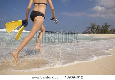 Caucasian woman carrying scuba equipment to water