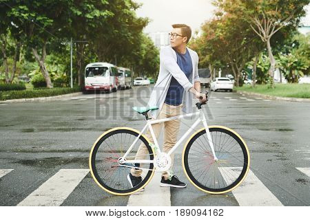 Handsome man with bicycle turning back when crossing road