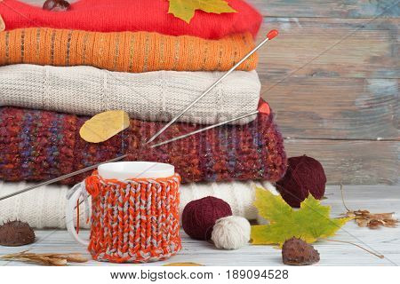 Knitted wool sweaters. Pile of knitted winter, autumn clothes on wooden background, sweaters, knitwear, ball, cup, leaf space for text