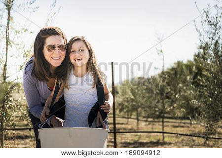 Caucasian mother and daughter smiling in olive grove