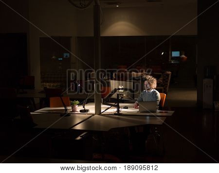 Young man working on computer at night in dark office. The designer works late