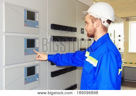 Engineer technician electrical equipment testing electrical cabinets with control panel. Engineer in white helmet starts industrial equipment