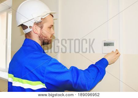 The engineer in the white helmet sets the temperature on the control panel of the air conditioner. Specialist in blue uniform and white helmet performs adjustment of air conditioning systems.