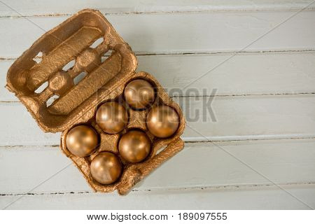 Golden Easter eggs in the carton on wooden background