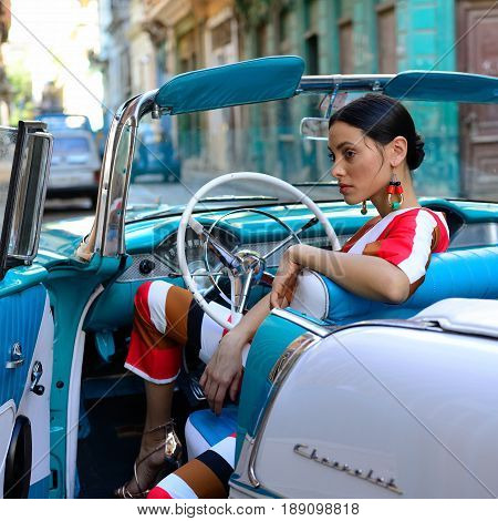 HAVANA CUBA - 11 DECEMBER 2016: Cuban woman is getting the classical American car off in the centre of old Havana