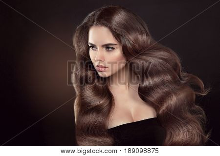 Healthy Hair. Wavy Hairstyle. Beautiful Brunette Woman Model With Clean Skin Advertising Shiny Brown
