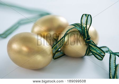 Close-up of golden Easter eggs tied with ribbon on white background