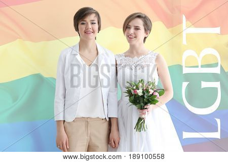 Happily married lesbian couple and rainbow flag on background. LGBT concept