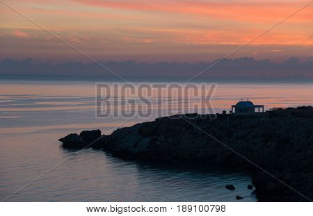Beautiful sunrise scene at Cape Greco (also known as Cavo Greco). Church silhouette is seen in the middle of composition.