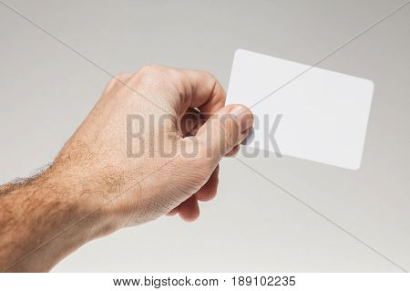 Male Hand Holds White Empty Card Over Gray