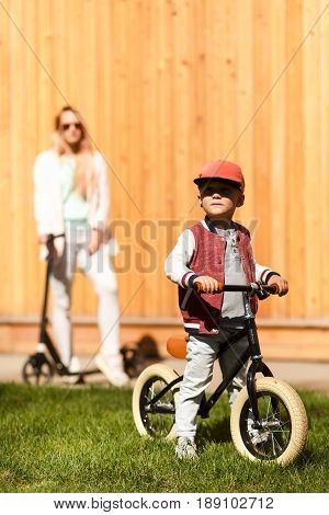 Mother with boy with cycles near wooden wall in park