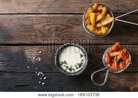 Variety of french fries traditional potatoes, sweet potato, carrot served in frying basket with white cheese sauce, salt, thyme over old wooden background. Top view with space. Homemade fast food
