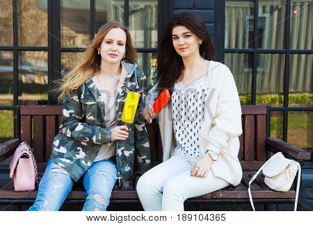 Two girls girlfriends dressed in fashion outfits rest, eat ice cream. Eskimo. Outdoor.