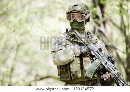 Photo of soldier in helmet with gun at forest