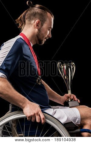 Paralympic In Wheelchair With Gold Medals On Neck Looking At Champion Goblet Isolated On Black