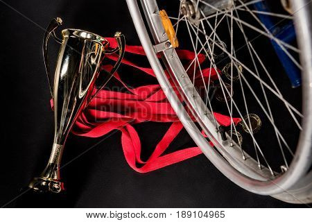 wheelchair standing on gold medals with red ribbons and champion goblet on black floor