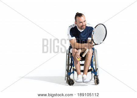 Smiling young man with tennis racquet sitting in wheelchair and looking away