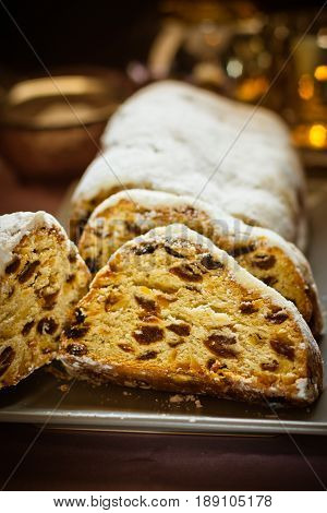 German Christmas stollen with raisins nuts candied fruits sliced powdered on plate festive table setting lit candle closeup