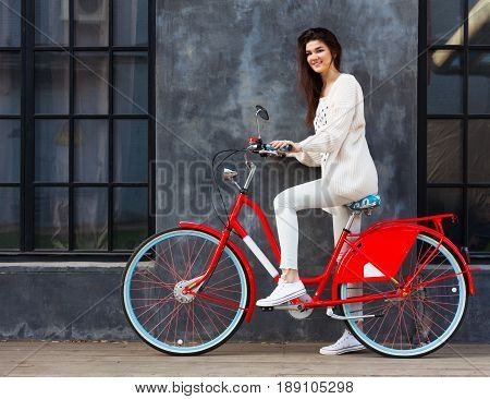 Streetstyle. Beautiful brunette girl in trendy, white outfit posing with a trendy vintage red bicycle outdoors. Outdoor.