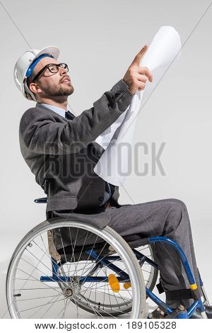 Physically Handicapped Architect At Wheelchair Holding Blueprint And Pointing With Finger