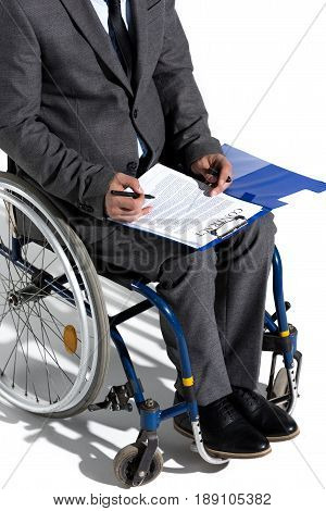 Cropped Shot Of Physically Handicapped Businessman In Wheelchair Signing Contract