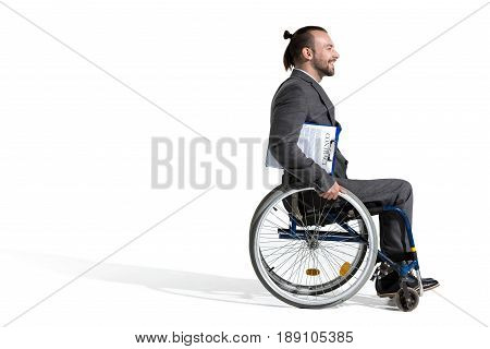 Physically Handicapped Businessman In Wheelchair Holding Clipboard Isolated On White