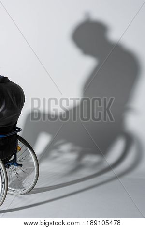 Cropped Shot Of Physically Handicapped Man In Wheelchair With His Shadow On Wall