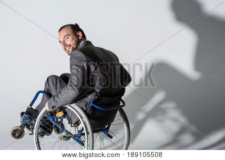 Young Physically Handicapped Businessman In Wheelchair With His Shadow On Wall