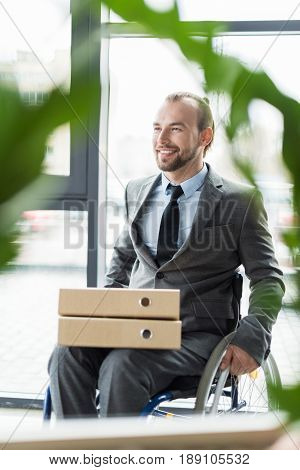 Young Smiling Physically Handicapped Businessman With Folders At Office