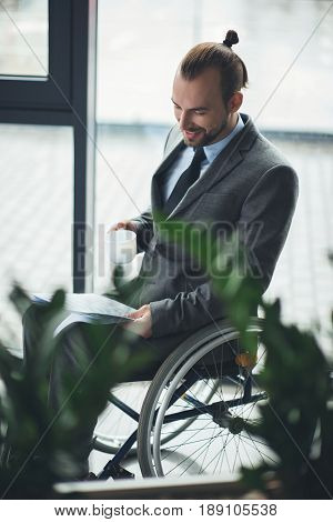 Smiling Businessman Sitting In Wheelchair Holding Cofee Cup And Looking At Documents In Office