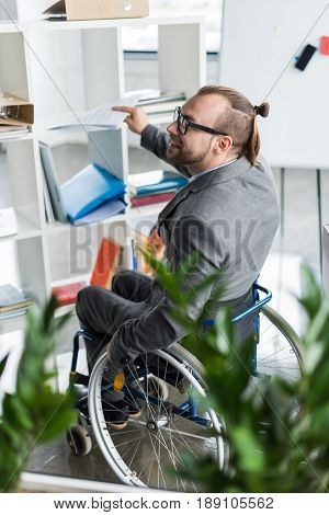 Young Physically Handicapped Businessman In Glasses Doing Paperwork At Office