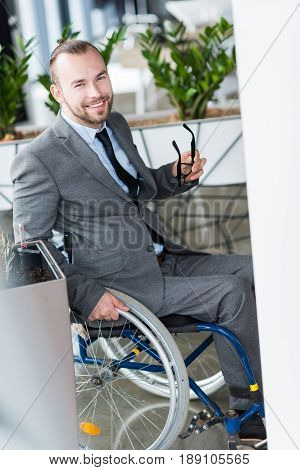 Smiling Physically Handicapped Businessman Holding Glasses And Looking At Camera