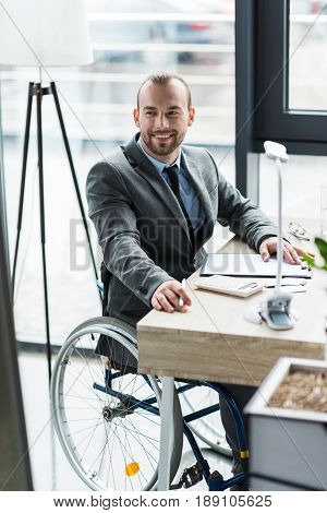 Smiling Physically Handicapped Businessman In Suit On Wheelchair Working At Office