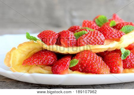 Delicious berry egg omelette. Home omelette stuffed with juicy strawberries and garnished with mint leaves on a plate and a wooden table. Healthy breakfast or brunch for kids and whole family. Closeup