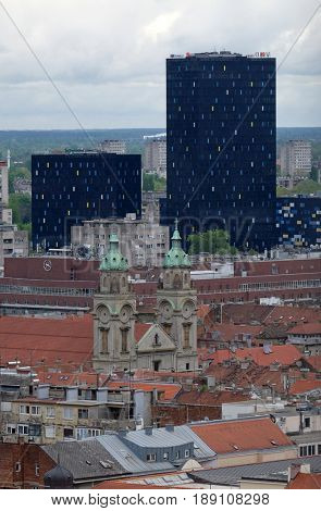 ZAGREB, CROATIA - APRIL 14: Basilica of the Sacred Heart of Jesus and the new metal and glass buildings in the center of Zagreb, Croatia on April 14, 2016