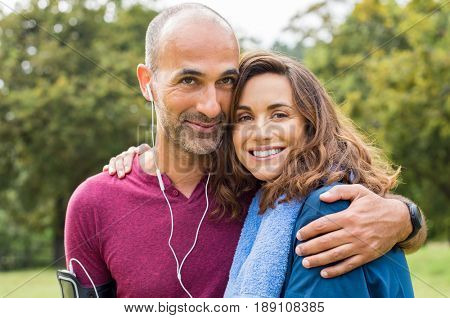 Sports couple having fun together at park. Portrait of a happy loving couple relaxing after fitness exercise outdoor. Portrait of multiethnic mature couple embracing and looking at camera.
