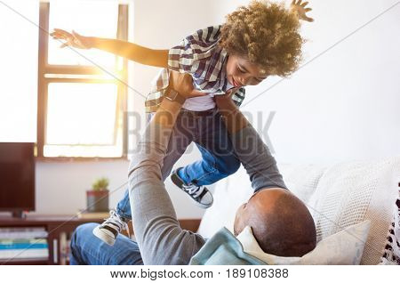 Cheerful young boy having fun with his father on sofa. Little african son playing with father on couch with open outstretched arms. Black child enjoying playing with dad at home.