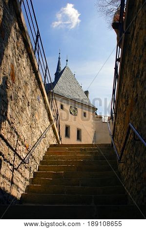 View on famous Czech castle Karlstejn in Gothic style clock tower, stair staircase architecture. Traditional european castle architecture. Perspective view on castle stair and tower
