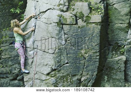 Young attractive female rock climber climbing challenging route on steep rock wall against scenic sunset background.
