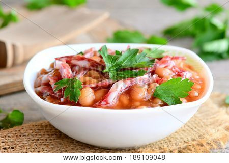 Easy white bean stew with smoked sausage, tomato sauce and fresh parsley in a bowl and on a wooden vintage table. Simple slow cooker white bean and smoked sausage. Homemade stew recipe. Closeup
