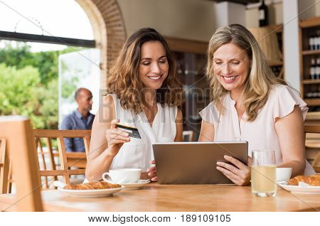 Mature friends buying on internet using a credit card. Happy friends booking and paying their next vacation with debit card on digital tablet in a cafe. Two middle aged women doing shopping online.