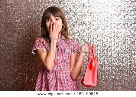 small pretty girl or cute fashionable child with long brunette hair and adorable surprised happy face in checkered dress with female red leather bag on metallic silver background copy space