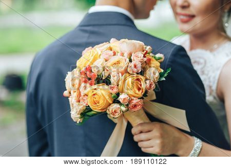 The bride in a white dress is standing next to her fiance and is holding a wedding bouquet