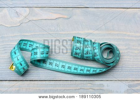 Roll Of Twisted Cyan Measuring Tape On Vintage Wooden Background