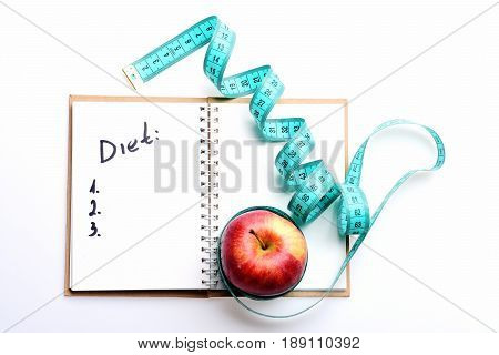 Notebook With Diet Plan And Twisted Blue Measuring Tape